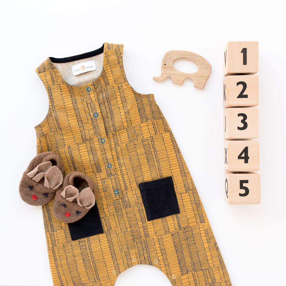 A Rain Dance Romper baby gift. A sleeveless romper with a front placket, bias bound armholes and neckhole, and crotch snaps for easy changing.